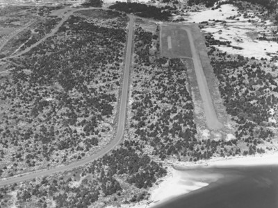 This image from 1978 shows ample space and trees at the south end of the air strip. In the 1980s, park staff cut the trees to create a more gradual angle of approach for aircraft. With vegetation gone, the coastline eroded close to the tarmac as it remains today.